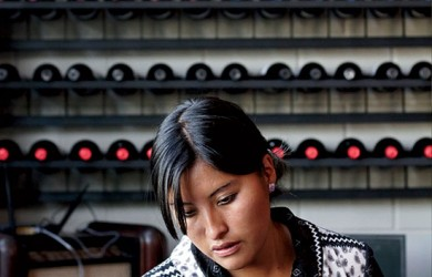 An employee is seen in front of a wine cellar at Gustu restaurant in La Paz